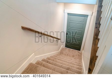 Stairway Inside Home With U Shape Design And Leads To The Wooden Basement Door
