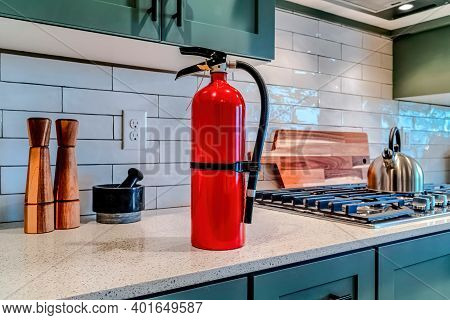 Red Fire Extinguisher Beside Cooktop On The Countertop Inside Kitchen Of Home