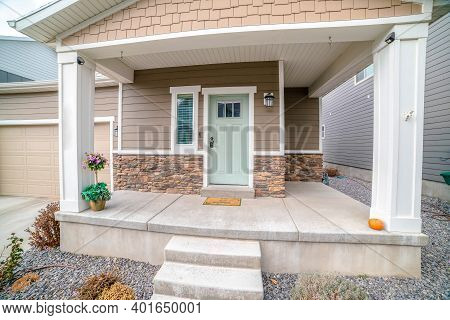 Front Door And Sidelight Against Brick Wall And Wood Siding Of Home With Porch