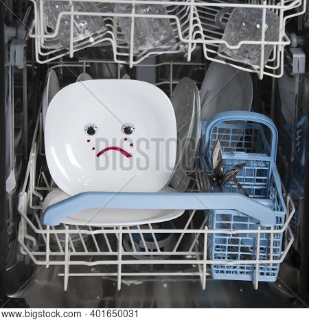 Poorly Washed Dishes In Dishwasher. Integrated Dishwasher With White Plates And Sad Emotion On Plate