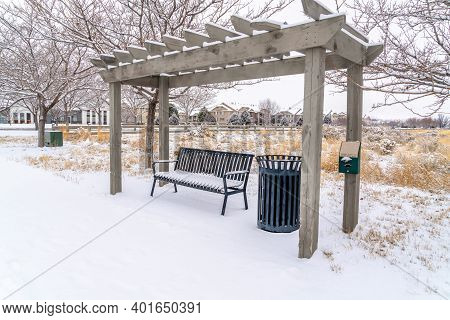 Metal Bench And Garbage Can Under Wooden Pergola On A Snowy Landscape In Winter