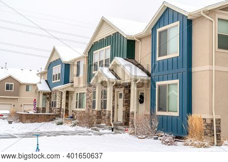 Snowy Yard In Front Of Apartment With Colorful Exterior Wall And Gabled Entrance