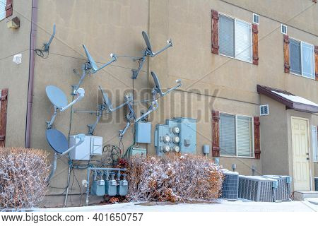 Building With Satellite Dishes Water Meters And Electricity Meters Against Wall