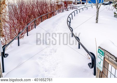 Pathway With Handrails Buried Under Snow In Winter At A Scenic Neighborhood