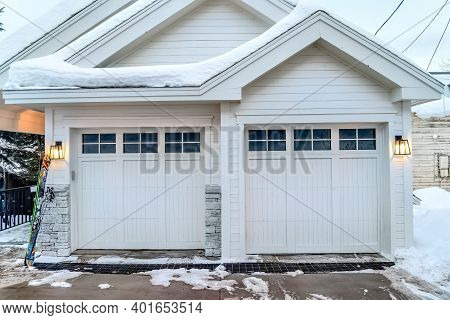 Home Exterior With White Walls Gabled Roofs And Two Glass Paned Garage Doors