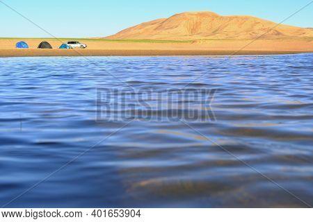 Camping on the large lake on edge of a sandy desert. Mongolia sandy dune desert Mongol Els near lake Durgen Nuur. Khovd province, Western Mongolia.