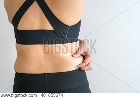 Women Body Fat Belly. Obese Woman Hand Holding Excessive Belly Fat. Diet Lifestyle Concept To Reduce