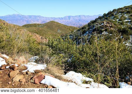 Snow Besides Chaparral Plants On A Windswept Mountain Ridge Overlooking The Arid High Desert Plateau
