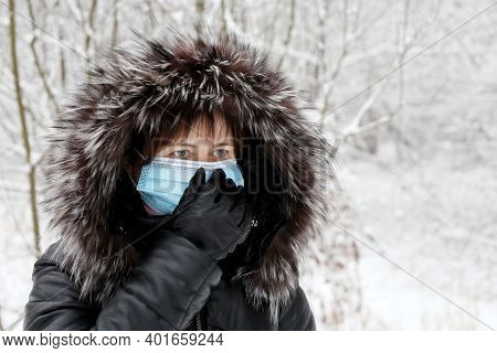 Coronavirus Protection, Woman In Medical Mask And Fur Hood Standing In Winter Park During Snow. Conc