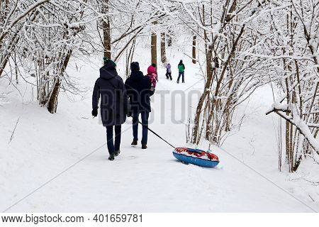 Family Leisure In Winter Park, Parents And A Child With Snow Tube. People Walking In Frosty Day