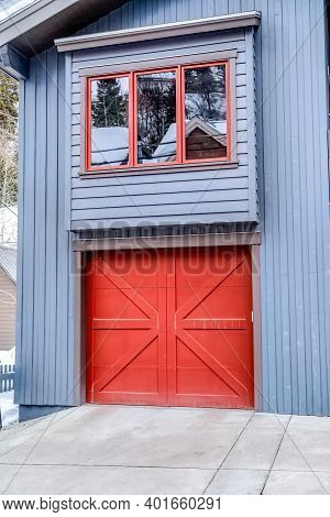 Door Of An Attached Single Car Garage Of Home With Gray Exterior Wall Siding