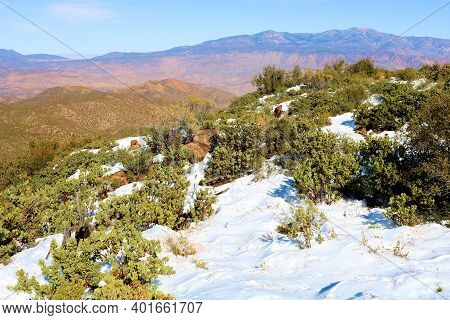 Snow Surrounded By Chaparral Plants On A High Desert Mountain Ridge Overlooking Arid Badlands Taken