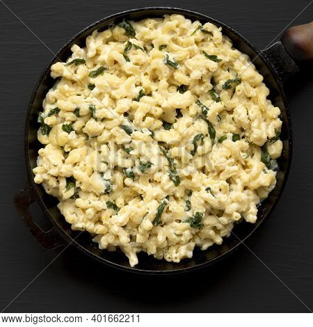 Homemade Spinach Mac And Cheese In A Cast-iron Pan On A Black Background, Top View. Flat Lay, Overhe