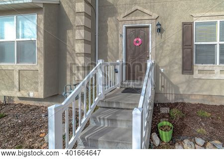 Home With Concrete Stairs Wooden Handrails And Brown Front Door At The Entrance