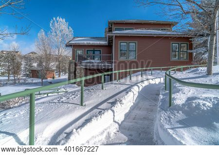 Snowed In Pathway With Metal Handrails Along House With Brown Exterior Wall