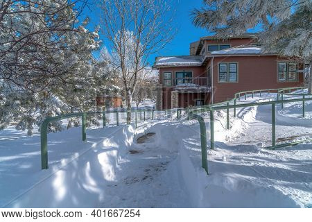 Pathways With Handrails And House On A Snowy Landscape On A Sunny Winter Day
