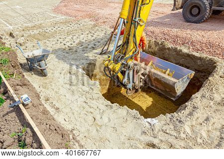 Worker Is Leap Out From Quadratic Trench With Little Help Of Digger's Bucket Full Of Excavated Groun