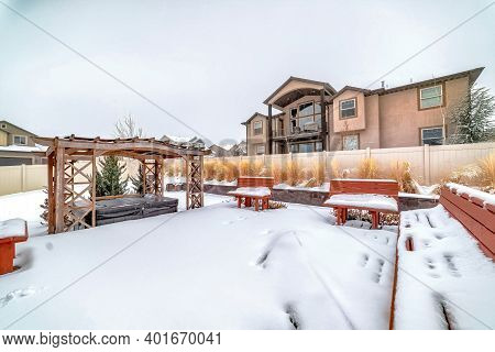 Frosted Backyard With Snowy Deck And Benches Overlooking A Wooden Pergola