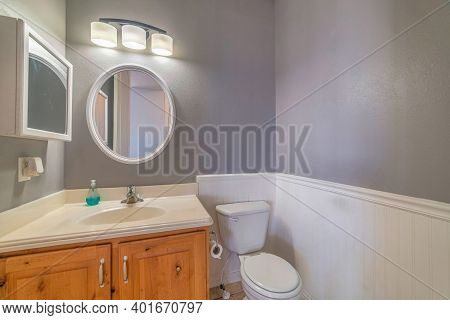 Toilet And Sink With Cabinet In A Residential Bathroom With Minimalist Design