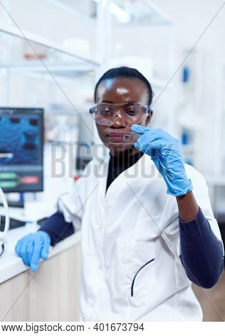 African Biochemistry Looking At Sample On Glass Slide With Protection Glasses During Medical Investi