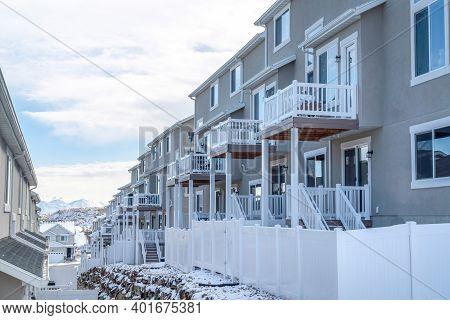 Townhouses On A Snowy Suburban Neighborhood Against Cloudy Blue Sky In Winter
