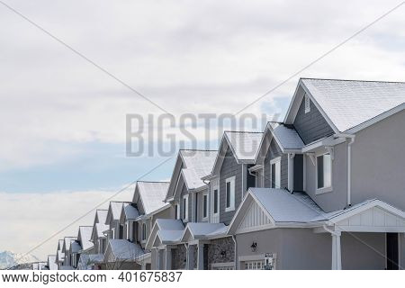 Townhouses With Snowy Gable Roofs In Winter On A Scenic Suburbs Community.