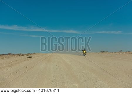 Motorcyclist On A Dirty Road In The Namib Desert, Namibia
