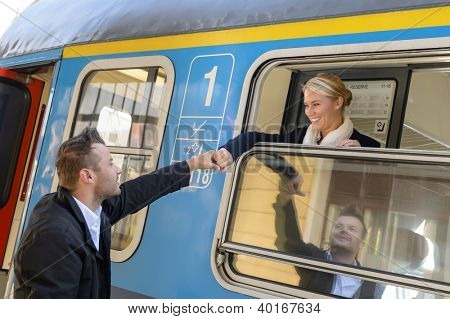 Woman leaving with train man holding hand goodbye smiling commuter