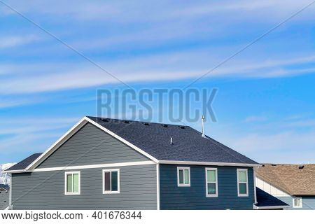 Exterior Of Upper Floor Of Home With Gable Roof And Gray Horizontal Wood Wall