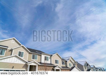 Townhouses On A Residential Neighborhood Landscape With Cloudy Sky Background