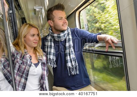 Couple looking out the train window smiling woman man vacation