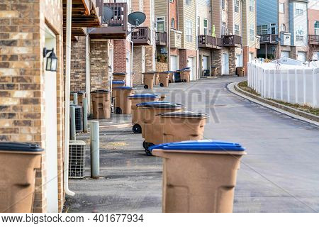 Garbage Cans On Road Along Townhouses With Balconies And Attached Garages