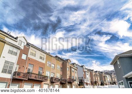 Dramatic Skyscape Of Cloudy Blue Sky Over Townhouses With Wasatch Mountain View
