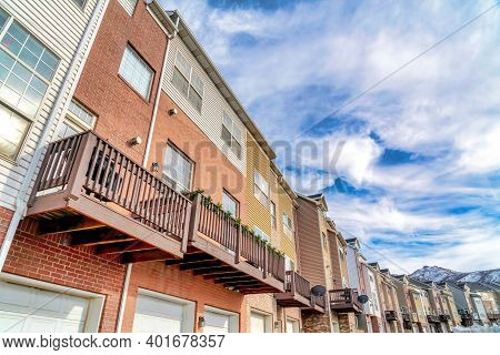 Townhouses With Balconies Over Garages Against Wasatch Mountain And Cloudy Sky