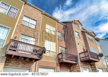 Townhouses Facade With Garage Doors Below Small Balconies With Satellite Dishes