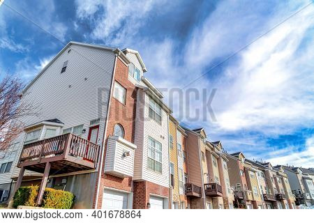 Exterior View Of Townhouses In The Valley Under Bright Clouds And Vivid Blue Sky