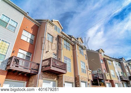 Sunny Day View Of Townhouses With Balconies Over Entrances To Attached Garages