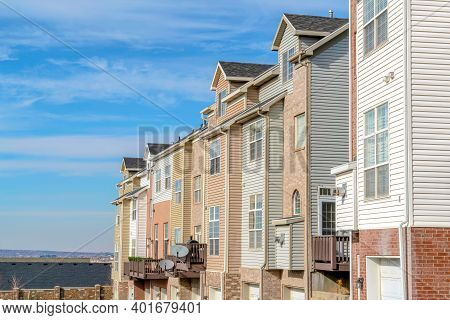 Townhouses On A Sunny Day Setting With Views Of Valley And Blue Sky With Clouds