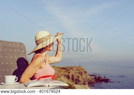 Mature Tourist Woman Relaxing On Coast With Book And Coffee Cup, Enjoy Sea View From Cliff. Reading