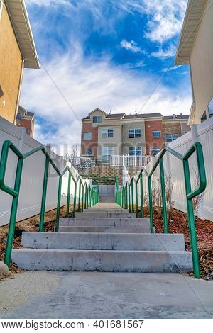 Stairway With Concrete Treads And Green Handrails Amidst Homes And Townhouses