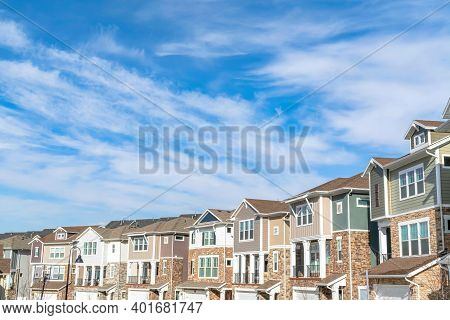 Three Storey Townhouses With Garages At The Facade Against Clouds And Blue Sky
