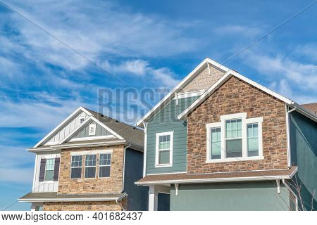 Gabled Homes With Stone Brick And Wooden Siding On Walls Against Cloudy Blue Sky