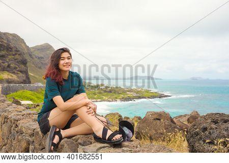 Biracial Asian Caucasian Teen Girl Sitting On Top Of Rock Stone Wall At Makapu'u Lookout Looking Out