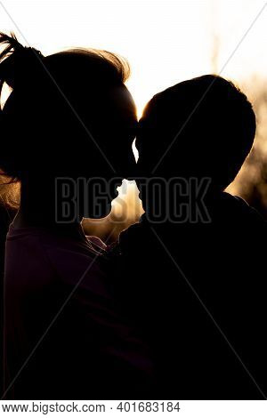 Silhouette Of A Mother And Son Playing Outdoors At Sunset. Mother's Day Concept