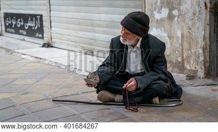 Yazd, Iran - May 2019: Old Muslim Beggar Man Sitting On A Street Of Yazd City