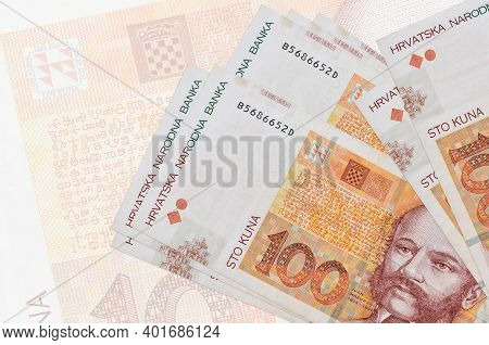 100 Croatian Kuna Bills Lies In Stack On Background Of Big Semi-transparent Banknote. Abstract Prese