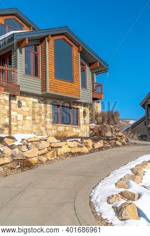 Exterior Of Home In Park City With Gray Siding And Stone Wall Against Blue Sky