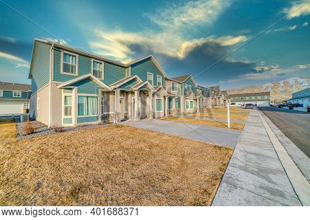 Townhouses With Teal Wooden Wall Against Snowy Mountain And Cloudy Sky