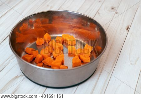 Metal Pet Bowl With Cut Carrot Inside. First Step Of Natural Organic Daily Meal Ration Preparation,
