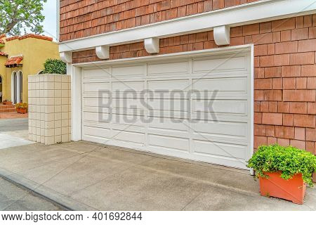 White Door Of Two Car Garage Of Home With Shingle Cladding On The Exterior Wall
